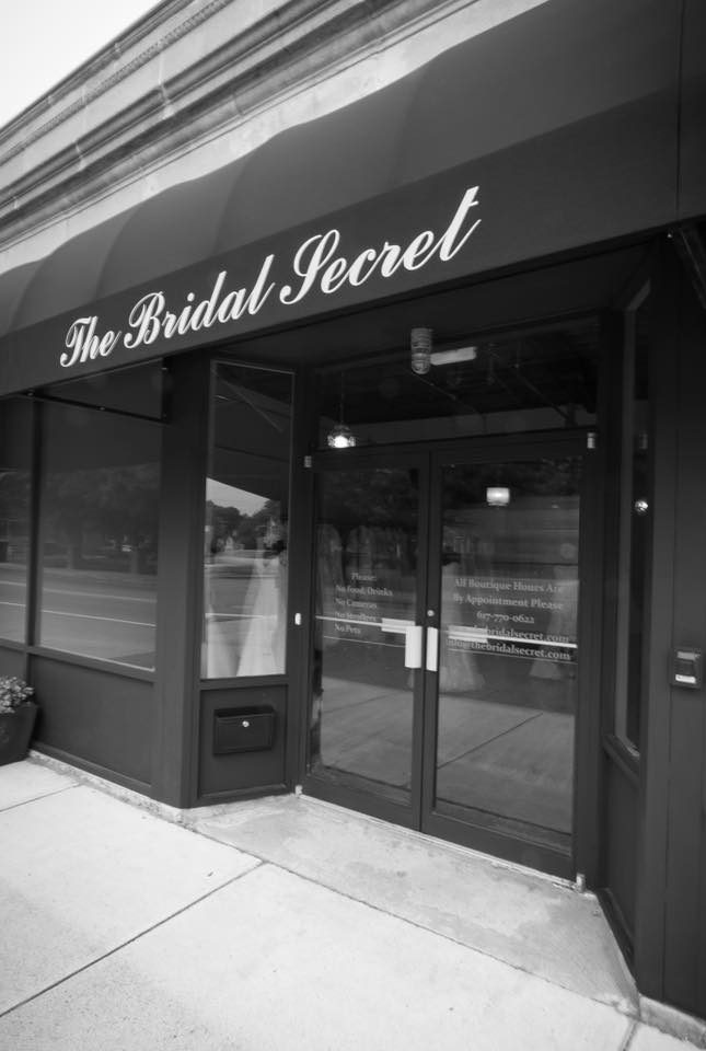 Exterior of The Bridal Secret Shop, glass front with two doors that pull out