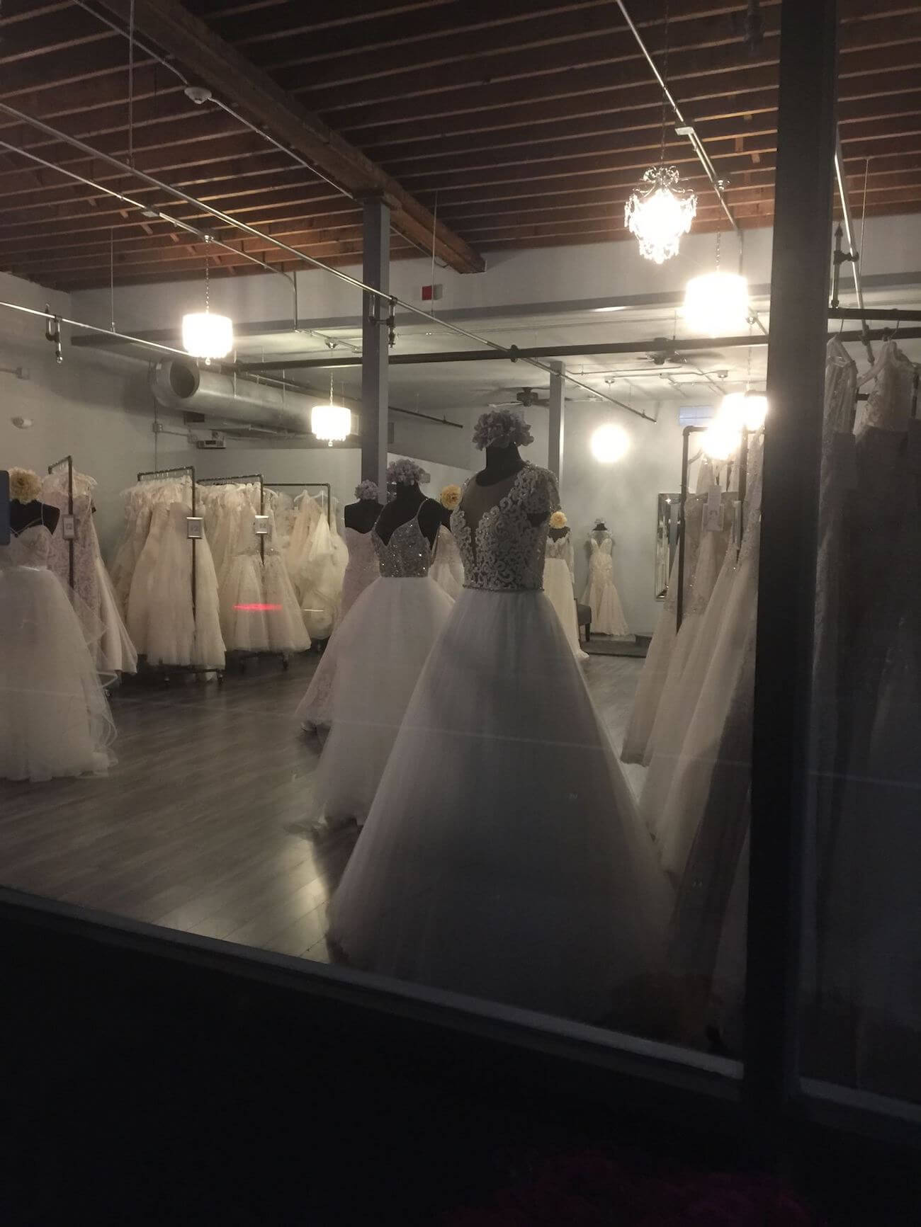Nighttime photo of The Bridal Secret, white gowns displayed on bodices with background lighting, wedding dresses on racks in distance.